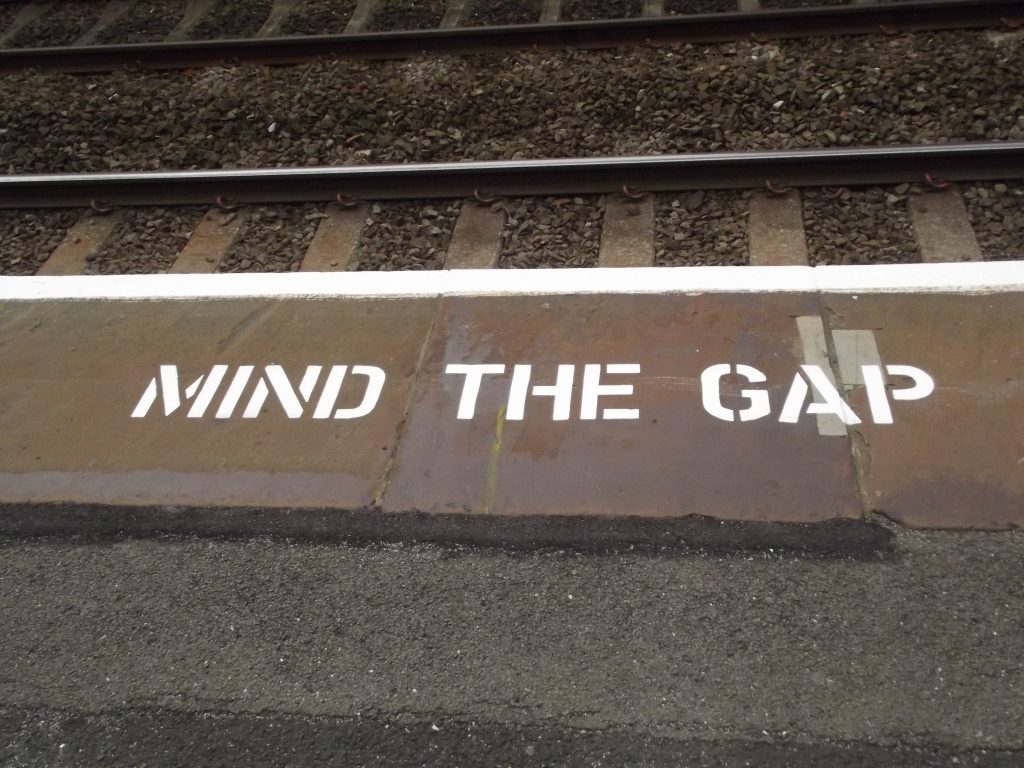"""Mind The Gap"" sign next to railroad tracks"