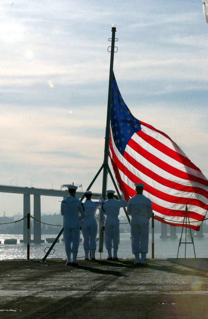 flag at half mast; sailor ssaluting
