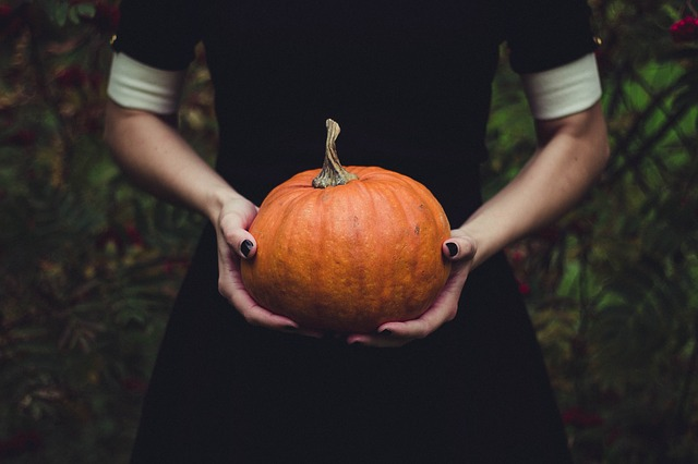 witch's hands holding a pumpkin