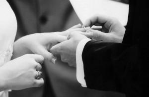 groom slipping ring on bride's finger
