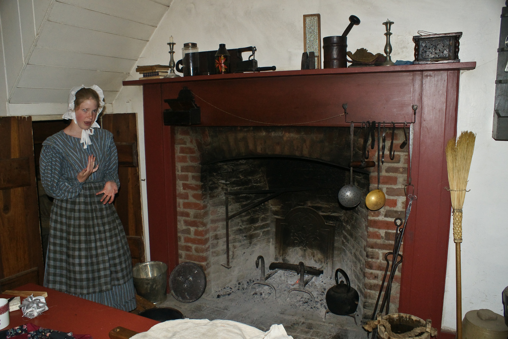 costumed woman by fireplace
